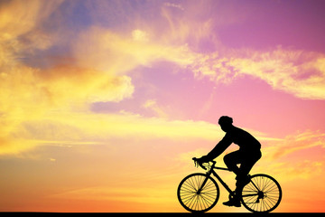 Silhouette man and bike relaxing on blurry sunrise background