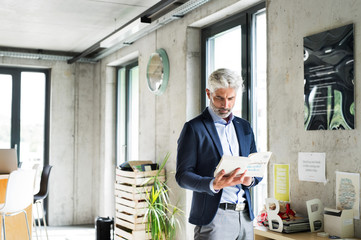 Businessman in creative office reading.