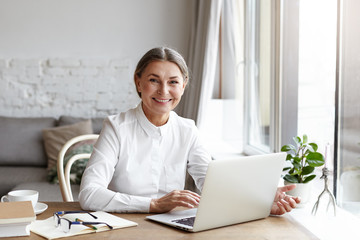 Happy mature woman psychologist or medical expert wearing white shirt working distantly on portable computer, consulting her clients online. Senior people, modern technologies, job and occupation
