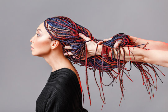 Colorful hair braids with kanekalon Zizi in the hands of a hairdresser, creativity and fashionable hairstyle concept