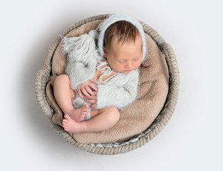Top view of newborn baby boy laying in a bowl
