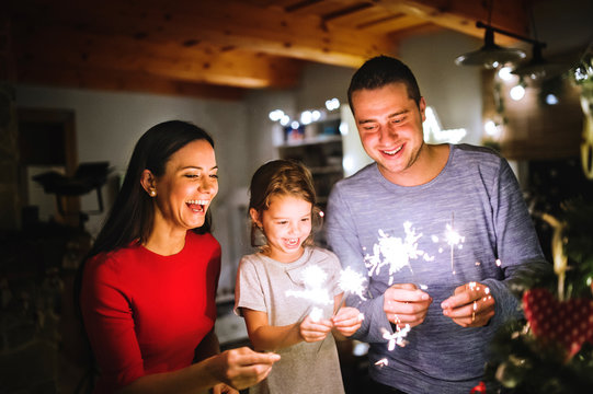 Young family with sparklers at Christmas time at home.