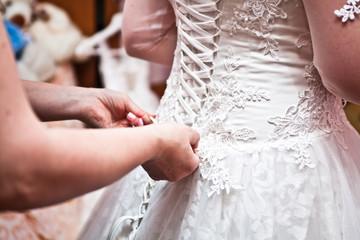 Mom helps the bride tighten the wedding dress corset