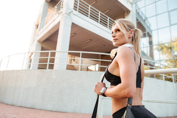 Pretty strong young sports woman standing outdoors