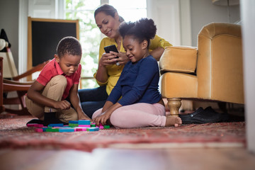 Mum using smartphone whilst children play