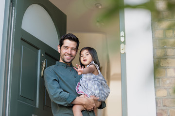 Father standing in home doorway with daughter waving