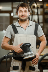 Smiling carpenter stand with eccentric grinding machine in hands