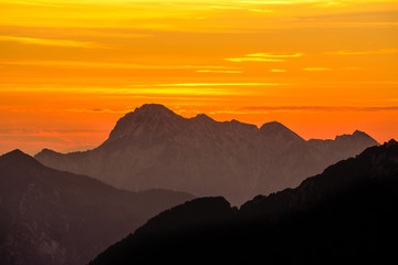 Wall Mural - Spectacular mountains silhouettes in orange sunset twilight. Julian Alps, Slovenia.