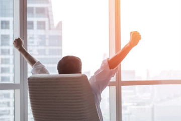 Business achievement concept with happy businessman relaxing in office room, resting and raising fists with ambition looking forward to city building urban scene through glass window