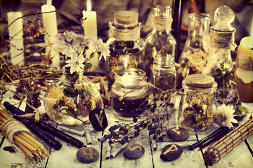 Healing herbs and berries, runes and candles on wooden table, toned image