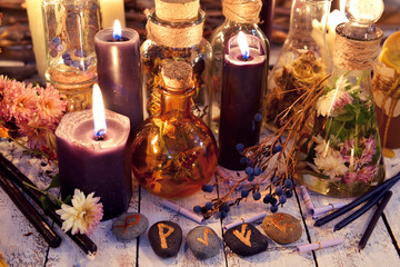 Magic runes, black candles, flowers and berries on witch table in candle light