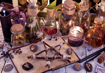 Wooden pentagram, open book, glass bottles, flowers, candles and runes on witch table