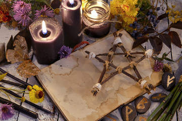 Black candles and pentagram on witch table