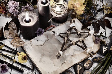 Open book with old empty pages, pentagram and black candles on witch table, toned image
