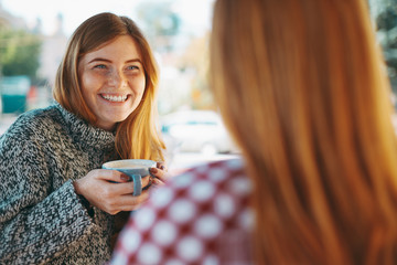 Smiling young women drinking coffee
