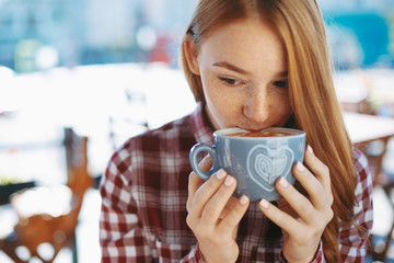 Close-up of natural reddish girl drinking a big cup of coffee