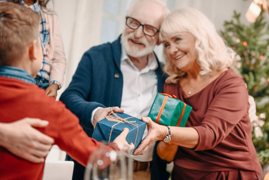 grandparents presenting gifts to grandson
