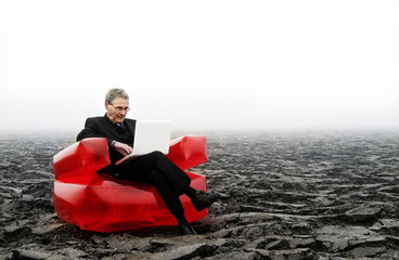 The Red Chair Business Serie: Senior Businessman in a Field on a big red seat working on his white laptop