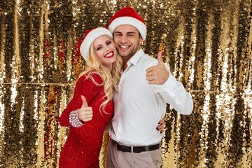 Portrait of smiling couple in red hats celebrating New Year