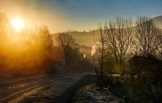road through mountain village at foggy sunrise. beautiful rural scenery in autumn