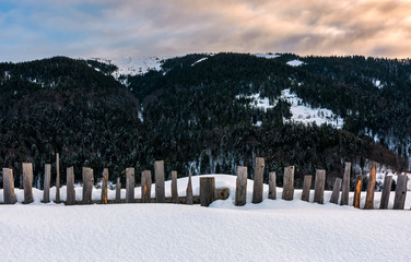 old wooden fence in snow on hillside. lovely mountainous rural scenery at sunrise