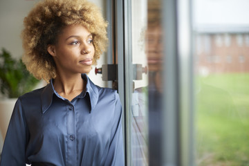 Laughing young afro-american woman standing at window at home