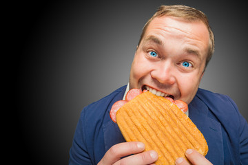 Funny hungry man eating the tasty sandwich
