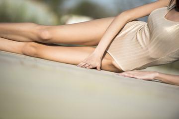 Slim women wear monokini lying in side on a wooden floor