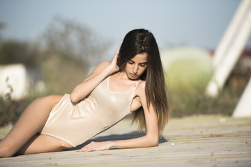 Slim women wear monokini lying in side on a wooden floor