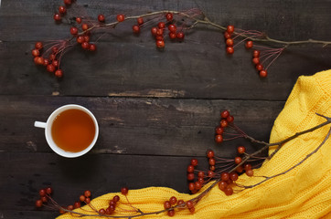 Autumn background boards with dark brown branches with small apples,  Cup of tea and a yellow sweater