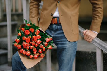 A bouquet of roses in male hands.