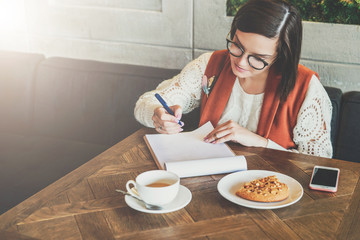 Young businesswoman in glasses and white sweater is sitting in cafe at table, working. Girl analyzes data, plans, considers income. Student learning online. On table cup of tea,smartphone. E-learning.
