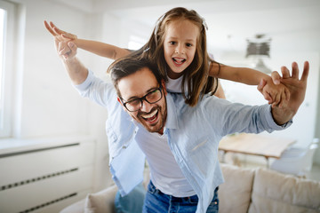 Portrait of father and daughter playing at home Wall mural