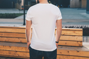 Summer day. Back view. Young bearded hipster man dressed in white t-shirt and sunglasses is stands on city street. Mock up. Space for logo, text, image. Instagram filter, film effect, bokeh effect.