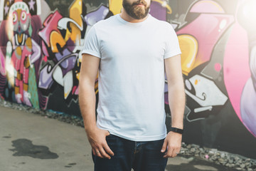 Summer day. Front view. Young bearded hipster man dressed in white t-shirt is stands against wall with graffiti. Mock up. Space for logo, text, image. Instagram filter, film effect, bokeh effect.