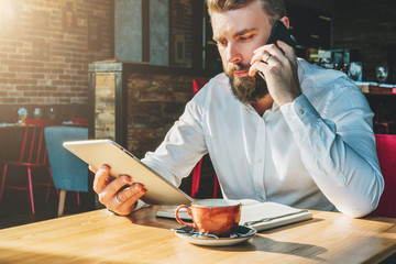 Young bearded businessman sits in cafe at table, talking on mobile phone, holding tablet computer.Man is working, studying.Online education, marketing,training.E-learning,e-commerce. Instagram filter.