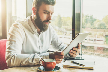 Young bearded businessman sits in cafe at table, holding tablet computer, working.On table cup of coffee, notebook, smartphone.Man is working,studying.Online education,marketing.E-learning,e-commerce.