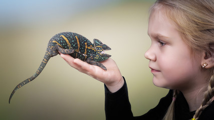 The child holds a bright hissing chameleon. Background nature