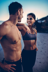 Fit happy caucasian adult couple together on the beach