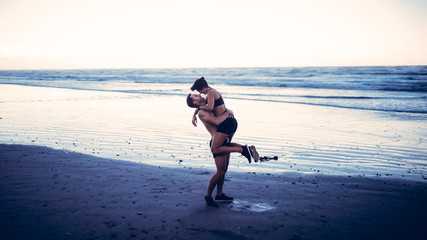 Young adult couple kissing on beach after run on beach