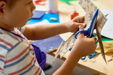 Portrait of cute little boy  cutting paper in arts and crafts class of pre-school making handmade gift
