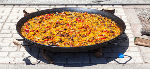 Paella. The national Spanish dish of paella in a large skillet is cooked on an open fire, at the stake.