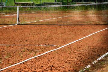 Tennis net at empty red gravel court