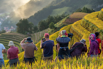 Undefined traveler taking photograph over the Rice fields on terraced of Mu Cang Chai District, YenBai province, Northwest Vietnam