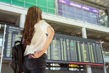 Closeup Asian woman traveler hand holding the passport for check-in at the flight information screen in modern an airport, lifestyle travel and transportation concept.