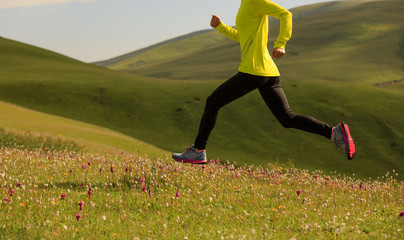 young fitness woman runner running on grassland mountain top