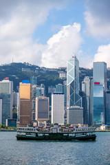 Hong Kong skyline and passenger ferry transportation on Victoria harbor at sunrise morning