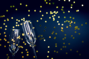 Two champagne glasses with star sprinkles on black. Holiday and celebration background. Luxury  party concept. Christmas and New Year Celebration