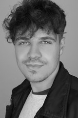Black and white fashion portrait photo of young and handsome man with curly hairstyle and leather jacket. Black and white male portrait of man with cute smile. Beautiful charming man possing to camera