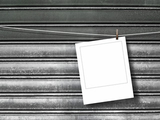 Blank square photo frame hanged by peg against gray metal shutter background